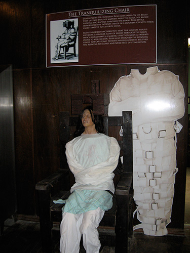 """The """"Tranquilizing Chair"""" where patients were restrained until they calmed down. Beside it is a full-body straight jacket."""