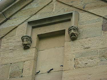 Carved faces, meant to ward off evil spirits. The Celtic masons hired to build the asylum believed evil could only enter through the back, so only the back entrances have these carvings.